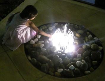 rock fountain, girl in fountain, girl by fountain, fountain with light, lighted fountain, playing in fountain, water fountain
