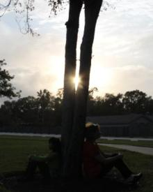 mom and daughter, sitting by tree, sun through trees, transracial adoption, international adoption, girl waiting, mom waiting, woman waiting, adoption